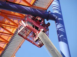 Man in basket fixing roller coaster