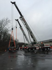 Crane lifting item onto tractor trailer