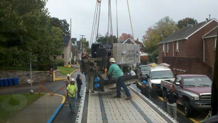 crew working to lift machinery on truck bed
